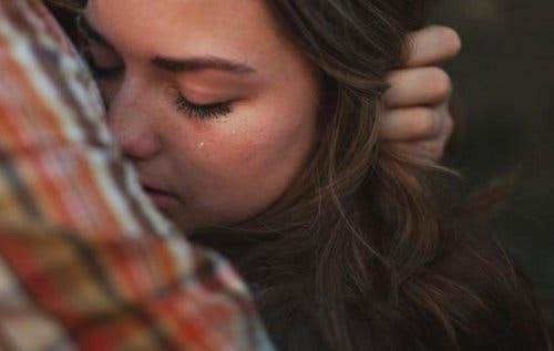 En kvinde, der græder på nogens skulder og sørger over en forsvundet person