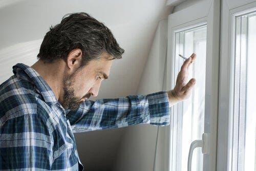 Mand, der står ved vindue og ryger