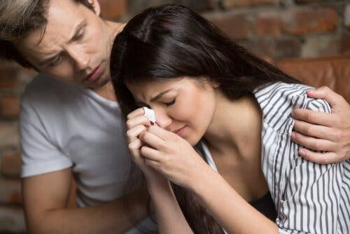Kvinde græder og trøstes af mand med bløde færdigheder