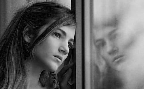Pige, der kigger ud af vindue