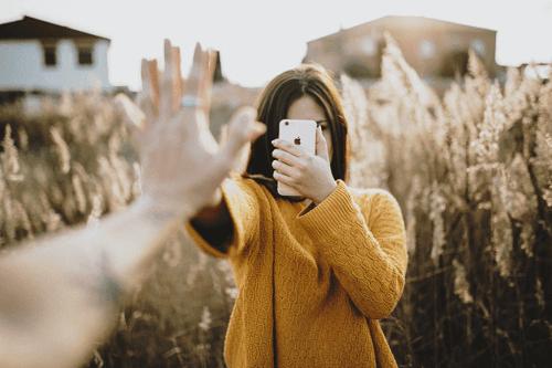 Personer rækker ud mod hinanden, men kvinde står med telefon i hånden som eksempel på, hvordan mobiltelefoner kan skade vores relationer