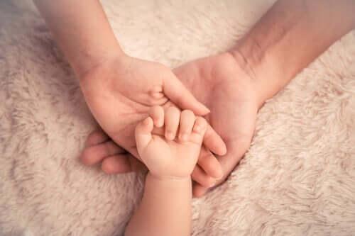 Babyhånd oven på voksenhænder