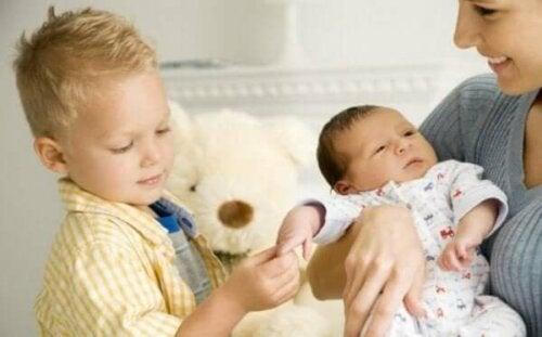 Dreng, der leger med lillebrors hånd i mors arme