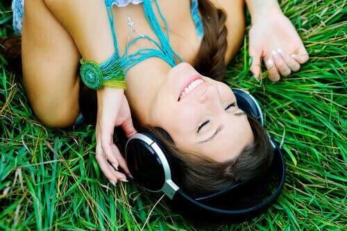 Glad kvinde på græs lytter til musik
