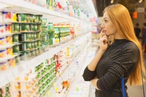 Kvinde, der kigger på varer i køledisk