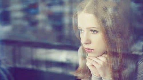 Kvinde, der kigger trist ud af vindue