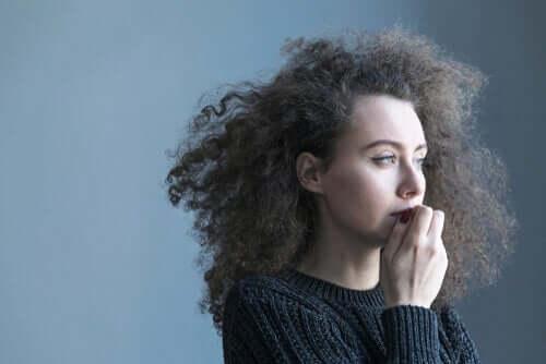 Kvinde er betænksom og tager sig til munden