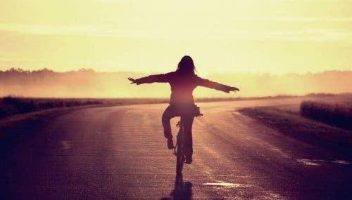 Kvinde cykler uden hænder på tom vej