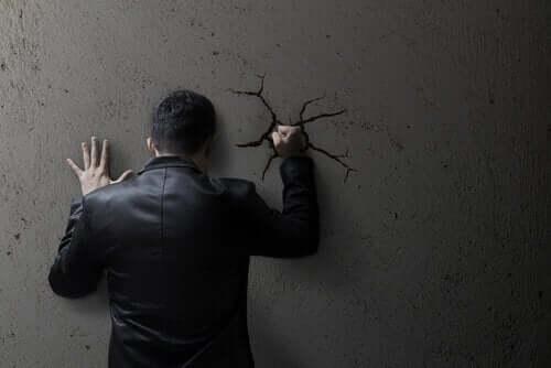Mand, der slår sin hånd ind i en væg