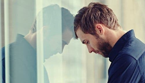 Mand hviler hoved mod vindue