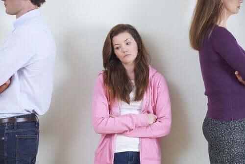 Pige imellem forældre, der står med ryggen til hende