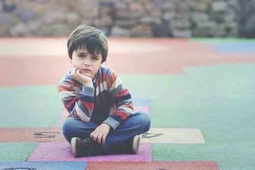 Trist dreng sidder på legeplads