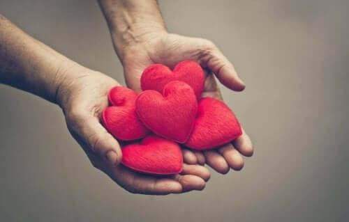 Et par hænder, der holder en bunke hjerter