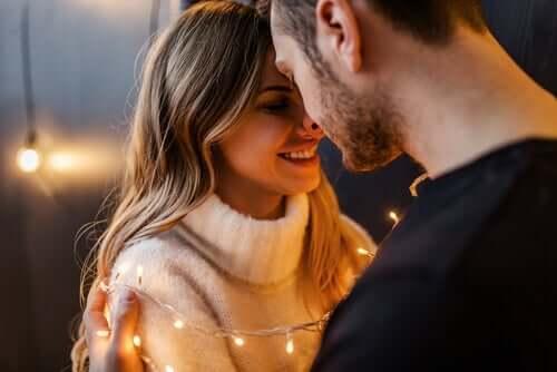 Forelsket par krammer med lyskæde omkring sig