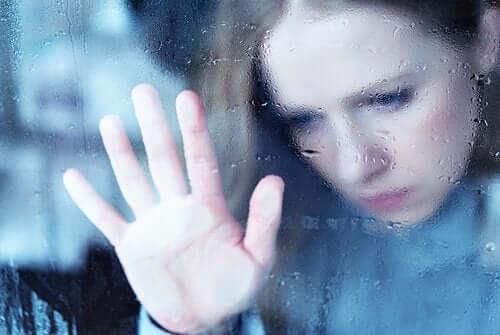 Kvinde, der holder hånd mod regnfyldt vindue