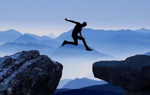 Mand, der hopper over en klippe