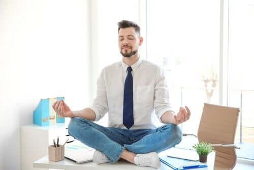 Mand, der mediterer på skrivebord