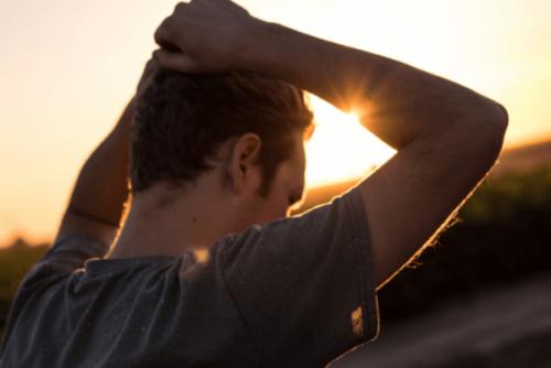 Mand foran sol har hænder over hovedet