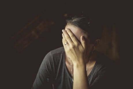 Kvinde gemmer ansigt bag hånd