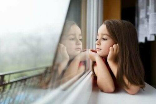 Pige kigger ud af vindue som symbol på børns frygt