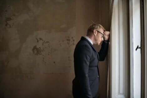 Frustreret mand, der læner sig op ad væg
