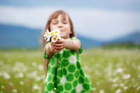 Pige på mark rækker blomster frem