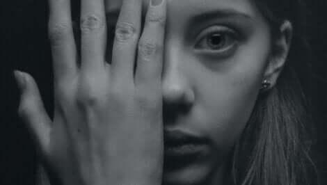 Kvinde, der holder sin hånd op foran halvdelen af sit ansigt