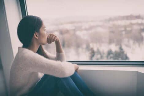 Kvinde, der kigger ud af vindue