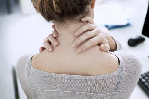 Kvinde tager aktive pauser på arbejdet ved at massere nakken