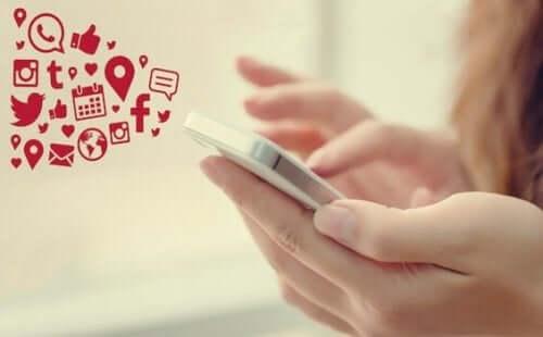 Pige bruger sin telefon til at tjekke sociale medier