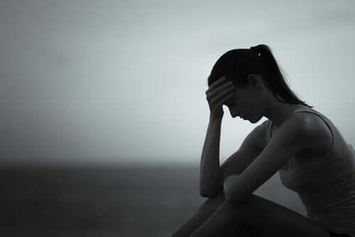 Trist kvinde, der tager sig til hovedet