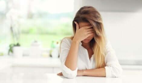 Trist kvinde ved køkkenbord