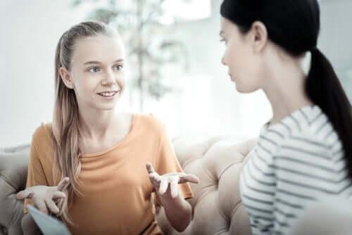 Unge kvinder, der snakker i sofa