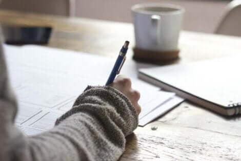 Person skriver på papirer