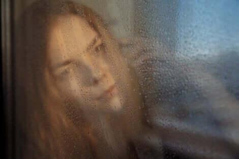 Trist kvinde bag dugget rude er offer for påtvunget glæde