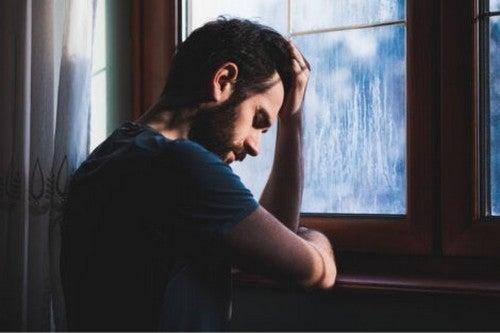 Mand sidder ved vindue og er ked af det