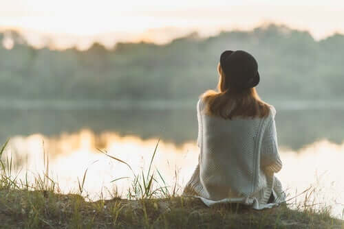 Kvinde, der sidder ved sø