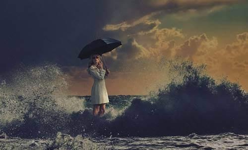 Kvinde, der står med en paraply i havet