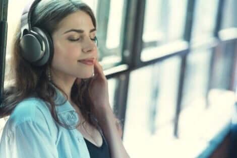 Kvinde lytter til musik i høretelefoner