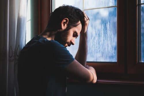 Trist mand ved regnfyldt vindue
