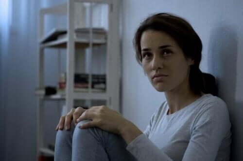Kvinde, der sidder op ad væg