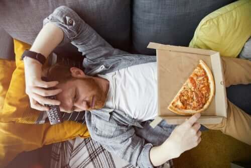 Mand ligger på sofa med pizza