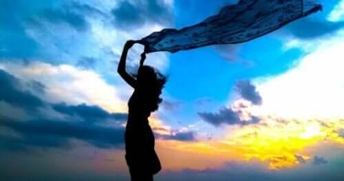 Silhuet af kvinde med tørklæde i vinden