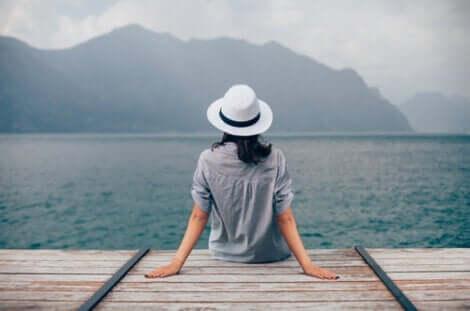 Kvinde, der sidder ved en sø
