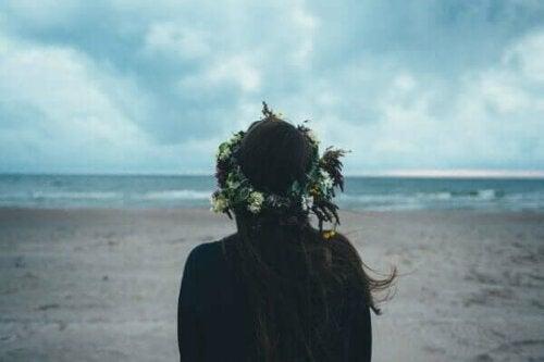 Kvinde med blomsterkrans i håret ved stranden