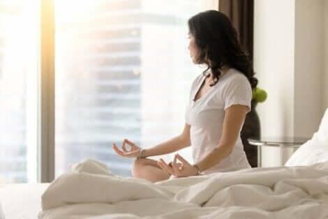 Kvinde mediterer på seng