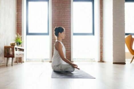 Kvinde mediterer i stue