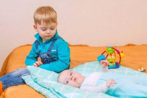 Lille dreng, der kigger på baby