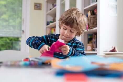 Lille dreng, der klipper i lyserødt papir