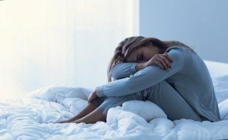 Træt kvinde, der sidder i seng